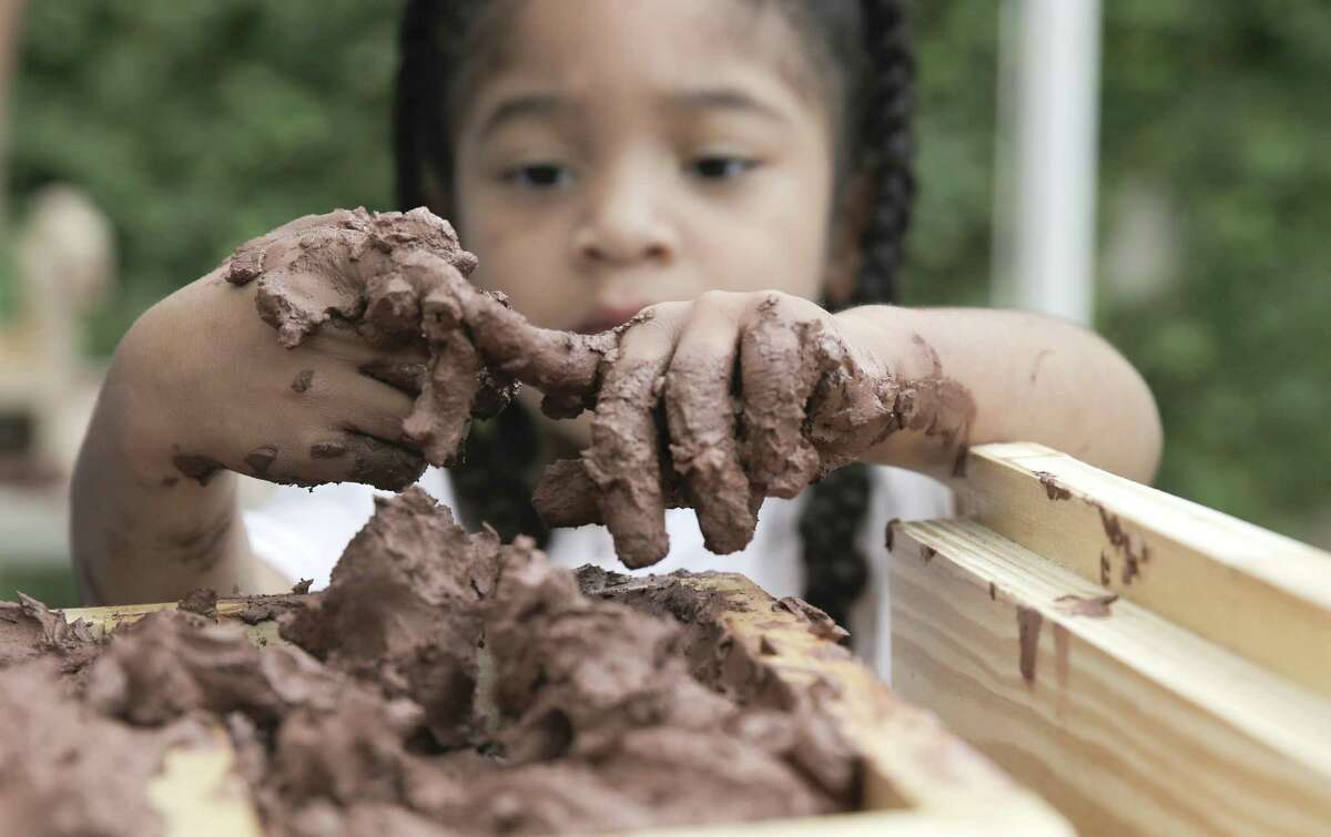 Laila Mixon, 4, wipes off her fingers while putting down clay to make bricks during a community brick making workshop, in the Houston's historic Freedmen's Town in the Fourth Ward on Saturday, June 22, 2019.