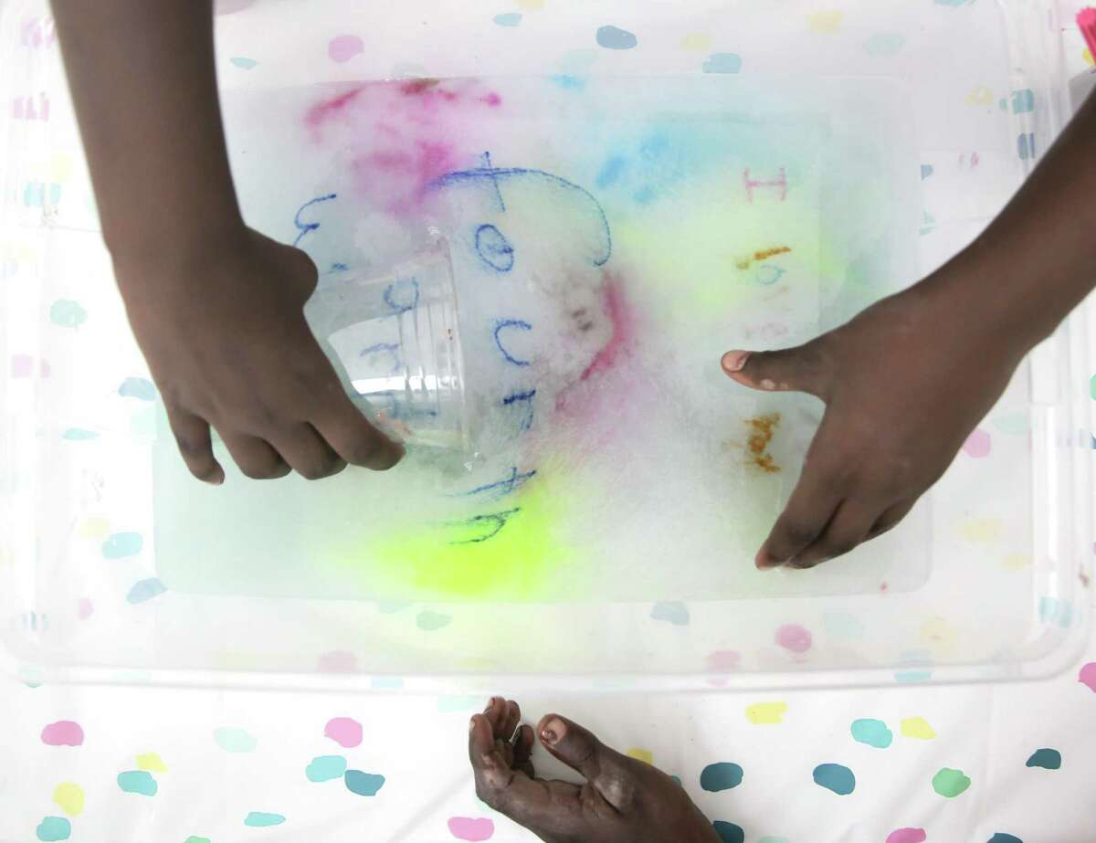 """Cherish Johnson, 8, scoops up her """"I love fourth ward"""" drawing as it dissolves into water to add to clay during a community brick making workshop in the Houston's historic Freedmen's Town in the Fourth Ward on Saturday, June 22, 2019."""