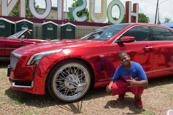 Steven Wells, 10, of Baytown, takes a photograph with a car at the Houston SLAB Holiday at 8th Wonder Brewery on Sunday, June 23, 2019, in Houston.