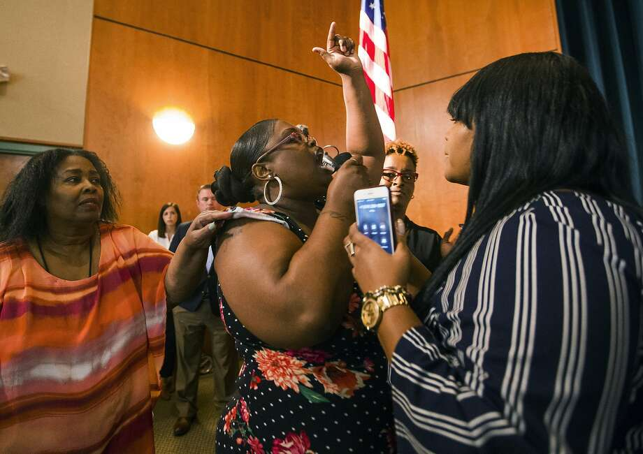 Komaneach Wheeler is restrained by family as she yells at Democratic presidential candidate and South Bend Mayor Pete Buttigieg during a town hall community meeting, Sunday, June 23, 2019, at Washington High School in South Bend, Ind. Buttigieg faced criticism from angry black residents at the emotional town hall meeting, a week after a white police officer fatally shot a black man in the city. (Robert Franklin/South Bend Tribune via AP) Photo: Robert Franklin, Associated Press