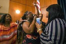 Komaneach Wheeler is restrained by family as she yells at Democratic presidential candidate and South Bend Mayor Pete Buttigieg during a town hall community meeting, Sunday, June 23, 2019, at Washington High School in South Bend, Ind. Buttigieg faced criticism from angry black residents at the emotional town hall meeting, a week after a white police officer fatally shot a black man in the city. (Robert Franklin/South Bend Tribune via AP)