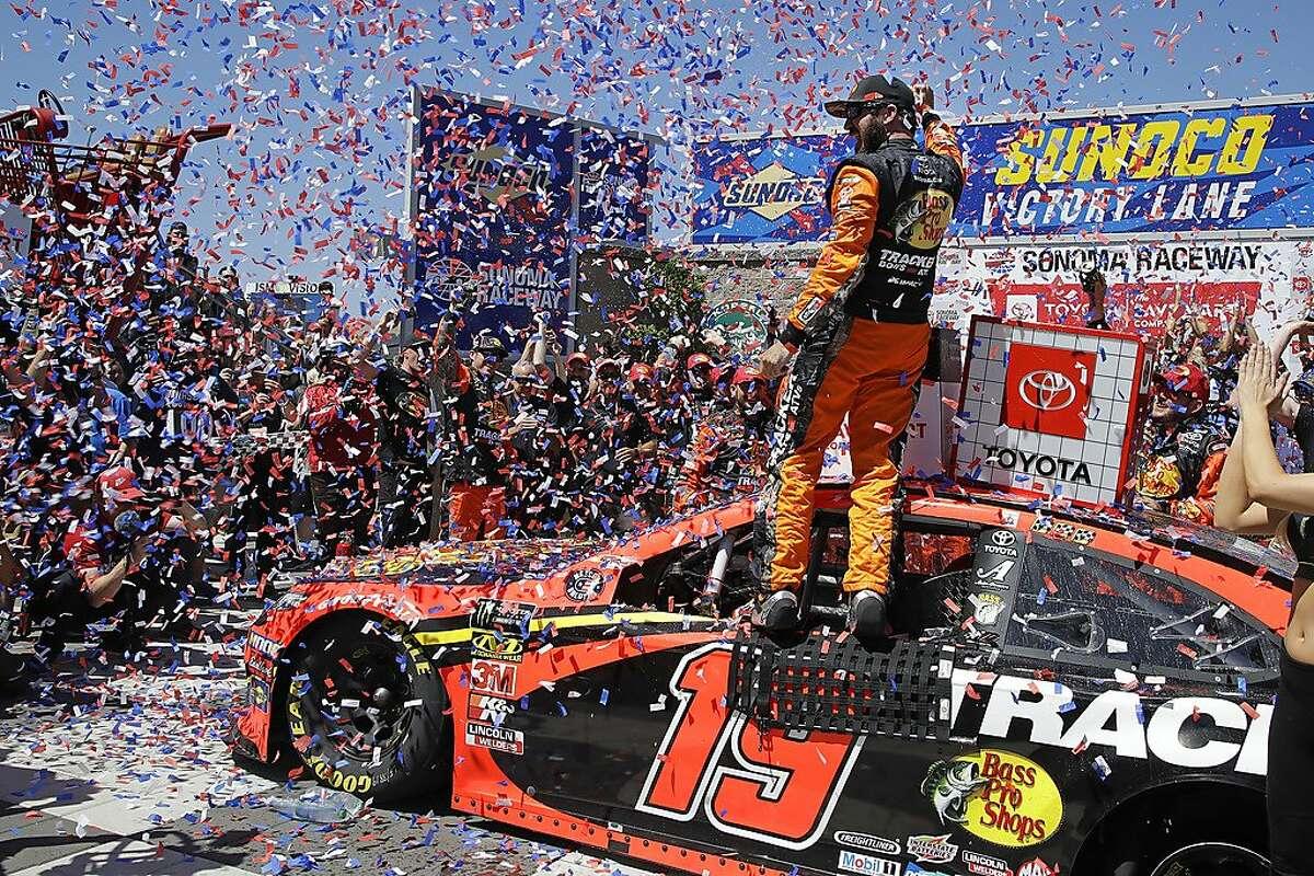 Martin Truex Jr. celebrates after winning a NASCAR Sprint Cup Series auto race in June 2019.