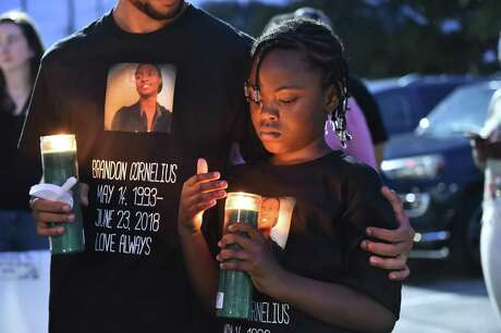 Francis Cornelius is hugged by her brother Patrick during a June 2019 candlelight vigil for their brother, 25-year-old Brandon Cornelius. Francis still wears the shirt.
