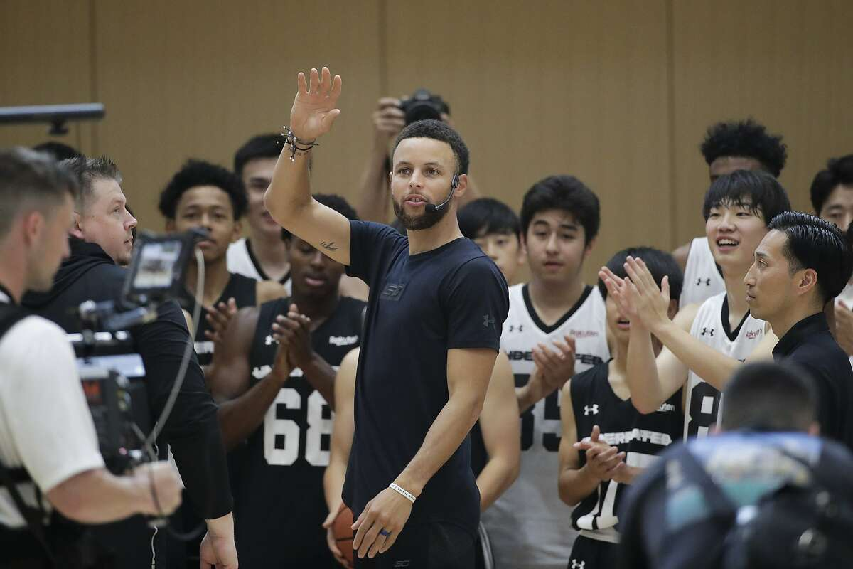 Golden State Warriors' Stephen Curry, center, waves toward the fans as he arrives to coach at a high school basketball camp Sunday, June 23, 2019, in Tokyo. Curry is already looking ahead to the next challenge in his basketball career, including the chance to represent the United States at next year's Tokyo Olympics. (AP Photo/Jae C. Hong)