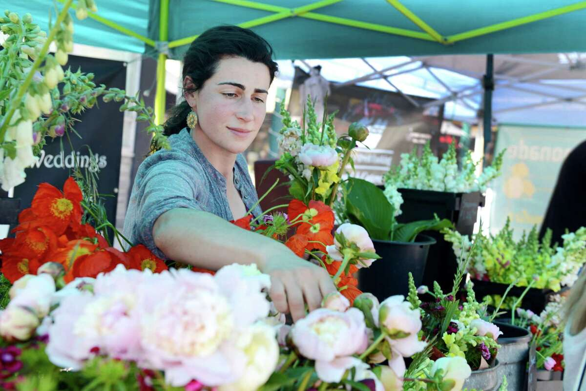 Emily Monahan of Cooperstown fixes a bouquet of flowers at her Art Farm Flowers stall at the Schenectady Greenmarket on Sunday, June 23, 2019, in Schenectady, N.Y. (Catherine Rafferty/Times Union)
