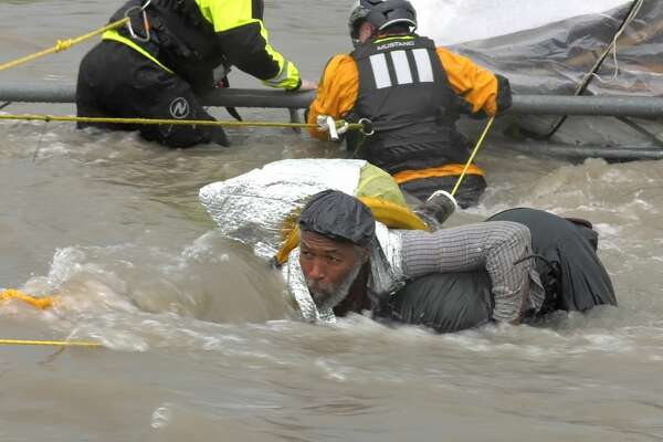 Houston firefighters rescue a homeless man who got caught in swift water in Brays Bayou underneath Texas Highway 288 on Monday, June 24, 2019.