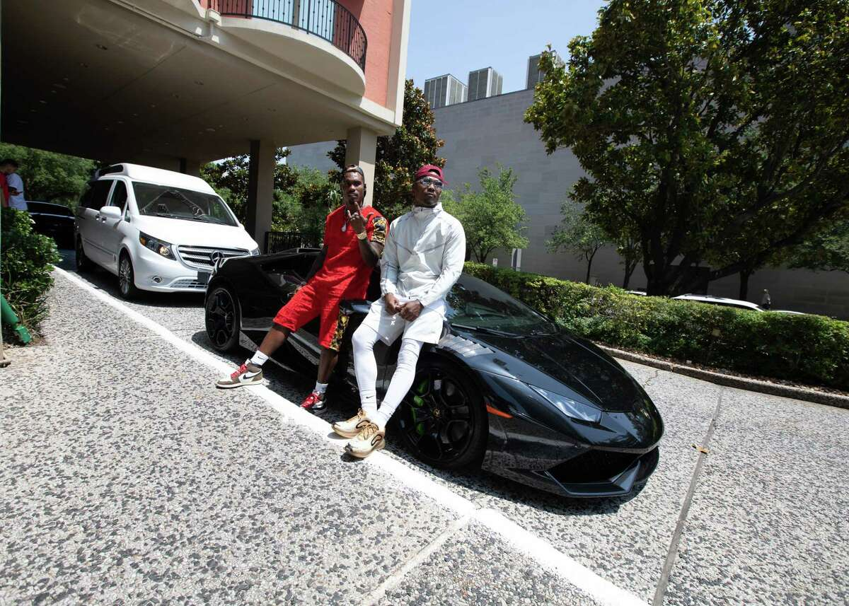 Twin brothers Jermall Charlo (left) and Jermell Charlo lean on Jermell's Lamborghini outside Hotel ZaZa in Houston on Thursday, May 30, 2019.