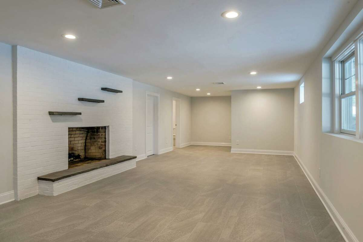 The full partially finished walk-out lower level has a fireplace and door to the backyard of this 3.15-acre level property.