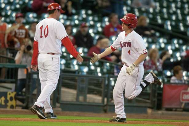 University of Houston designated hitter Cory Kay (4) is congratulated by third base coach Ryan Shotzberger after hitting a solo home run during the third inning of the Houston College Classic against Arkansas at Minute Maid Park on Saturday March 3, 2012 in Houston, TX.