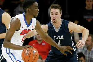 SMU guard Shake Milton (1) moves the ball around the perimeter as Yale's Jack Montague (4) defends during an NCAA college basketball game, Sunday, Nov. 22, 2015, in Dallas. (AP Photo/Tony Gutierrez)