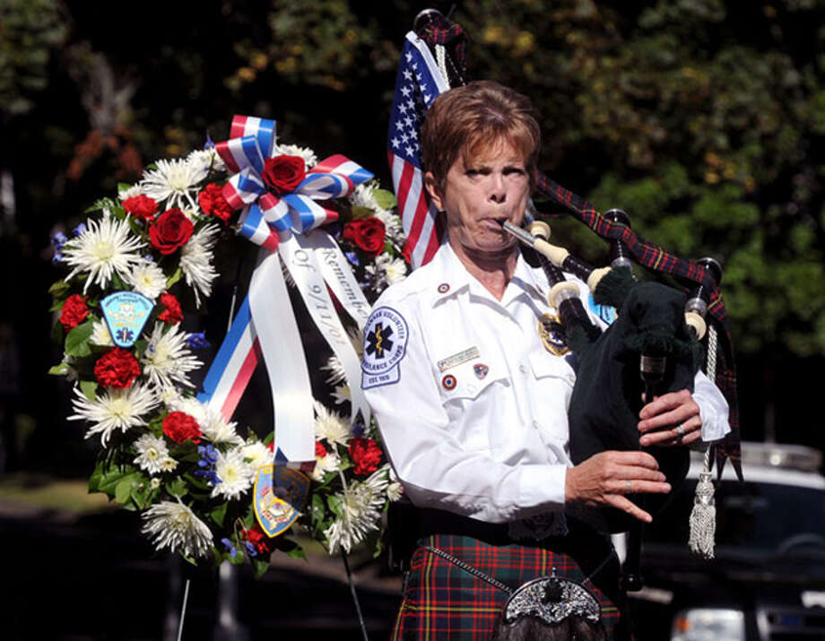 Stephanie Moore of the New Canaan Ambulance Corps plays the bagpipes during the town's Sept. 11 ceremony this morning at Vine Cottage. Participants observed the day there and across the street at the firehouse where the Sept. 11 memorial sits.