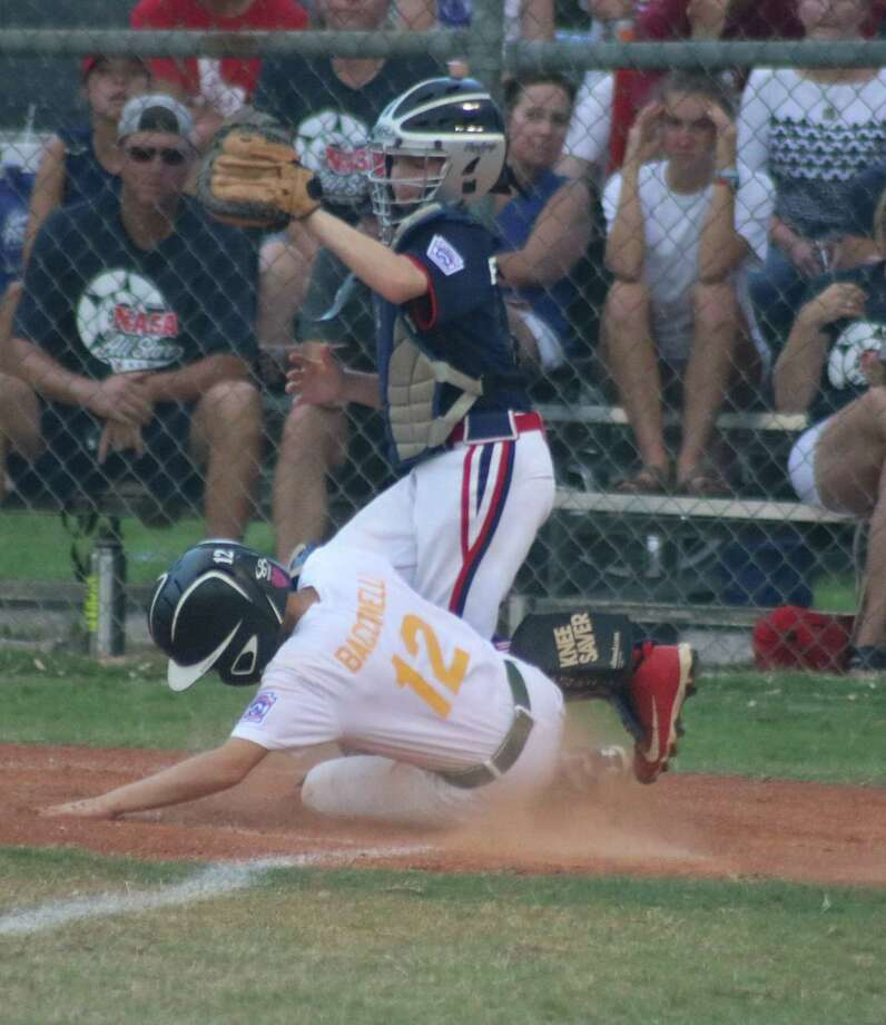 Santa Fe's Johnathen Baccinelli scores what proved to be the winning run, sliding home in the fifth inning to give Santa Fe its first lead of the game. Photo: Robert Avery