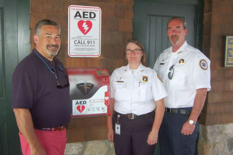 New AED devices have been installed at Greenwich Point thanks to a partnership between GEMS and the Friends of Greenwich Point. From left, friends member Phil Broes, GEMS Executive Director Tracy Schietinger and GEMS Deputy Director Patrick O'Conner pose by one of the new devices, which is at the concession stand in the old barn building. Photo: Ken Borsuk / Hearst Connecticut Media / Greenwich Time