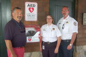 New AED devices have been installed at Greenwich Point thanks to a partnership between GEMS and the Friends of Greenwich Point. From left, friends member Phil Broes, GEMS Executive Director Tracy Schietinger and GEMS Deputy Director Patrick O'Conner pose by one of the new devices, which is at the concession stand in the old barn building.