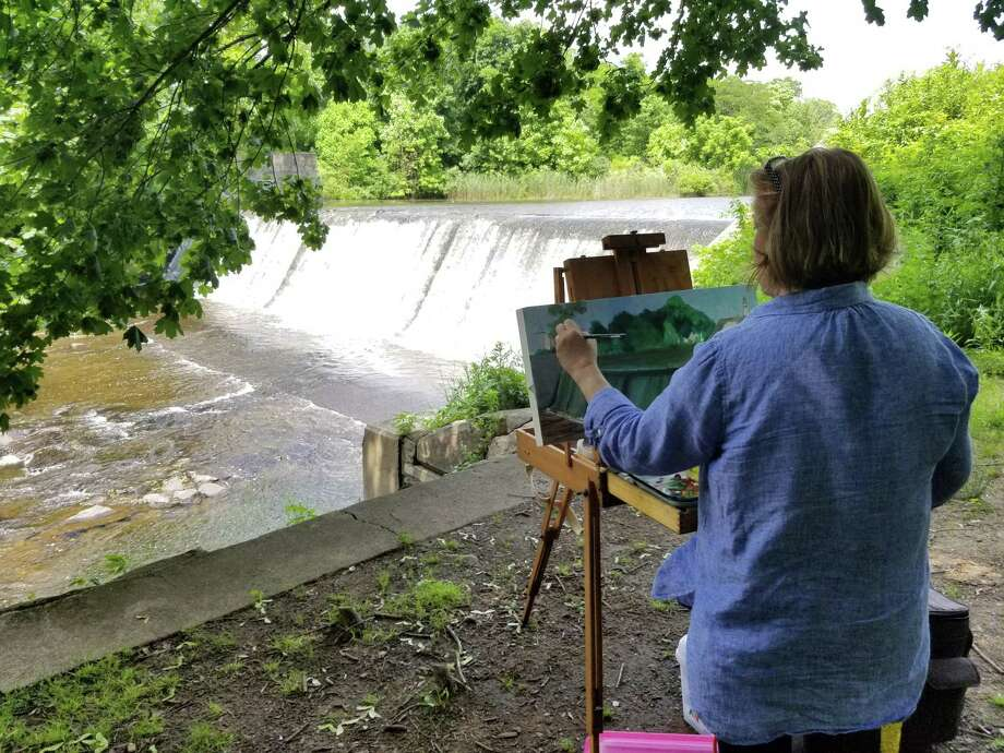 The Heritage Land Trust held a Paint Out at the Dam at Coe Dam Park June 22. Above, Mary Smealie works on her painting. She and other participating artists will sell their works of art at an upcoming auction July 12 at the Inn at Mount Pleasant in Torrington, donating a portion of the proceeds to the land trust. Photo: John Hislop / Contributed Photo /
