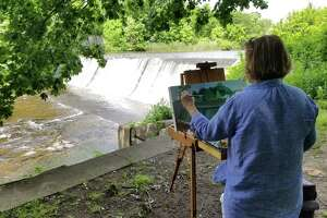 The Heritage Land Trust held a Paint Out at the Dam at Coe Dam Park June 22. Above, Mary Smealie works on her painting. She and other participating artists will sell their works of art at an upcoming auction July 12 at the Inn at Mount Pleasant in Torrington, donating a portion of the proceeds to the land trust.