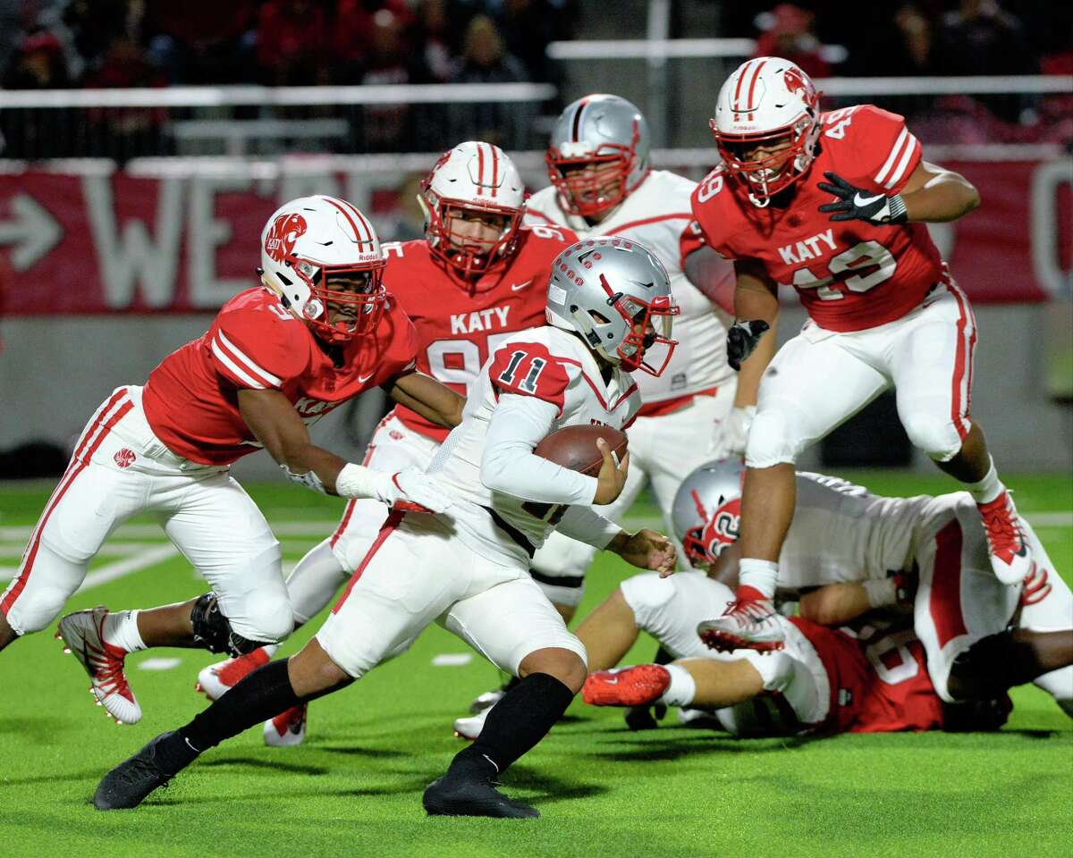 Eric Rodriguez (11) of Travis carries the ball on a quarterback keeper in the second quarter of a Class 6A Div. I Reg. III bi-district playoff game between the Katy Tigers and the Travis Tigers on Friday, November 16, 2018 at Legacy Stadium, Katy, TX.