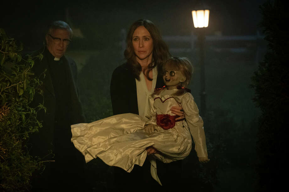 """Vera Farmiga, right, carries the titular devil-doll in """"Annabelle Comes Home,"""" as Steve Coulter, left, playing a priest, prepares to sprinkle the cursed toy with holy water. Photo: Handout Photo By Justin Lubin/Warner Bros. Pictures / For The Washington Post"""