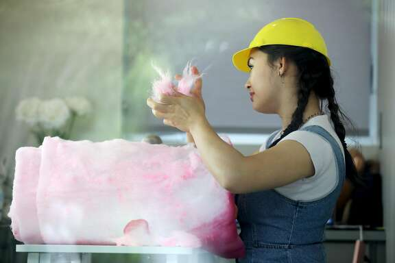 "ASMR artist Eve Donnelly, 17, shoots a video in her studio where she pretends to eat insulation, but she's strategically placed pieces of cotton candy away from the camera, in Palo Alto, Calif., on Tuesday, May 21, 2019. Donnelly has been shooting the ASMR (autonomous sensory meridian response) videos since December. ""So, I go under the guise of someone who's doing ASMR, but then once you actually see my videos you're like, 'Whoa, this is quite different than regular ASMR I would see.' My whole schtick is like eating things that aren't edible,"" Donnelly said. ""I guess my motivation is I want to get, like, a reaction out of people."""