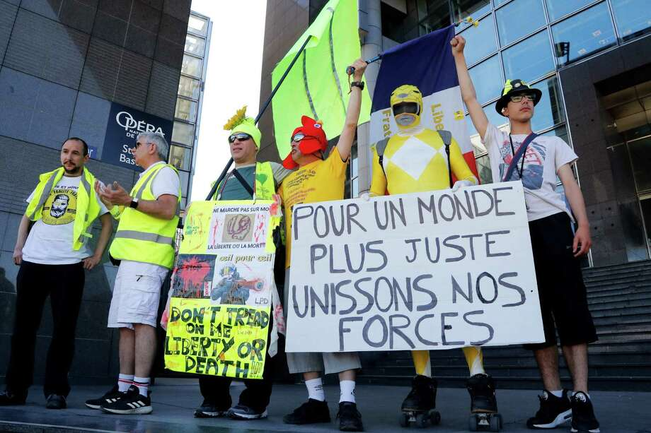 """Protesters, some of them claiming to have been seriously injured during the last six months Yellow Vest (Gilets Jaunes) demonstrations, hold a placard reading in French """"Join our forces for a more just world"""" on June 2 in Paris. These demonstrators are part of the reason France is not making much headway on climate change policies. Photo: FRANCOIS GUILLOT /AFP /Getty Images / AFP or licensors"""