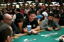 """Jeopardy!"" champion and professional sports gambler James Holzhauer, center, plays in a tournament at the World Series of Poker, Monday, June 24, 2019, in Las Vegas."