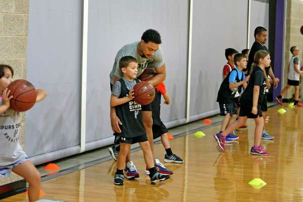 Bryn Forbes gives instruction to Brandon Hasan, 8, during the Spurs Summer Basketball Camp on Monday at St. Mary's Hall.