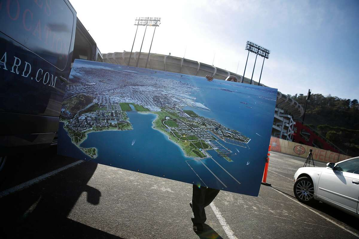 Tadesse Dereje, shuttle driver, puts a vision rendering for the Candlestick Point development project into a vehicle after a press conference in the Candlestick Park parking lot on Monday, November 17, 2014 in San Francisco, Calif.