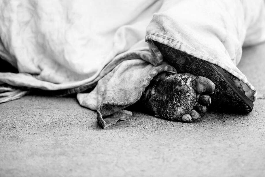 A man sleeps on a sidewalk at Mission and Second streets in S.F. on June 18. Photo: Noah Berger / Special To The Chronicle
