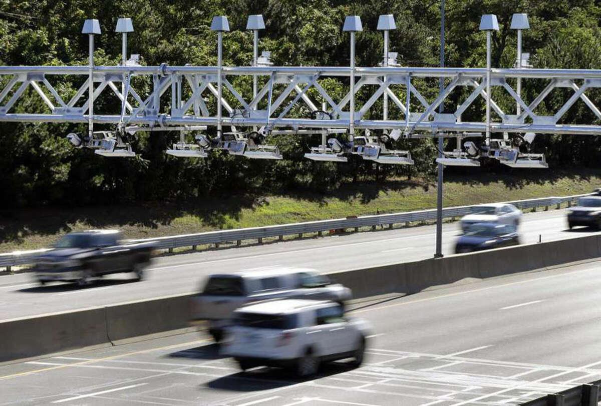 Cars pass under toll sensor gantries hanging over the Massachusetts Turnpike in Newton, Mass. Elise Amendola / Associated Press