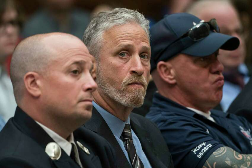 FILE - In a Tuesday, June 11, 2019 file photo, entertainer and activist Jon Stewart, center, lends his support to firefighters, first responders and survivors of the September 11 terror attacks at a hearing by the House Judiciary Committee on Capitol Hill in Washington.Stewart used his buddy Stephen Colbert?s late-night show Monday, June 17, to keep the heat on Senate Majority Leader Mitch McConnell for passage of legislation to replenish a victims' fund for first responders to the 9/11 attacks. (AP Photo/J. Scott Applewhite, File)
