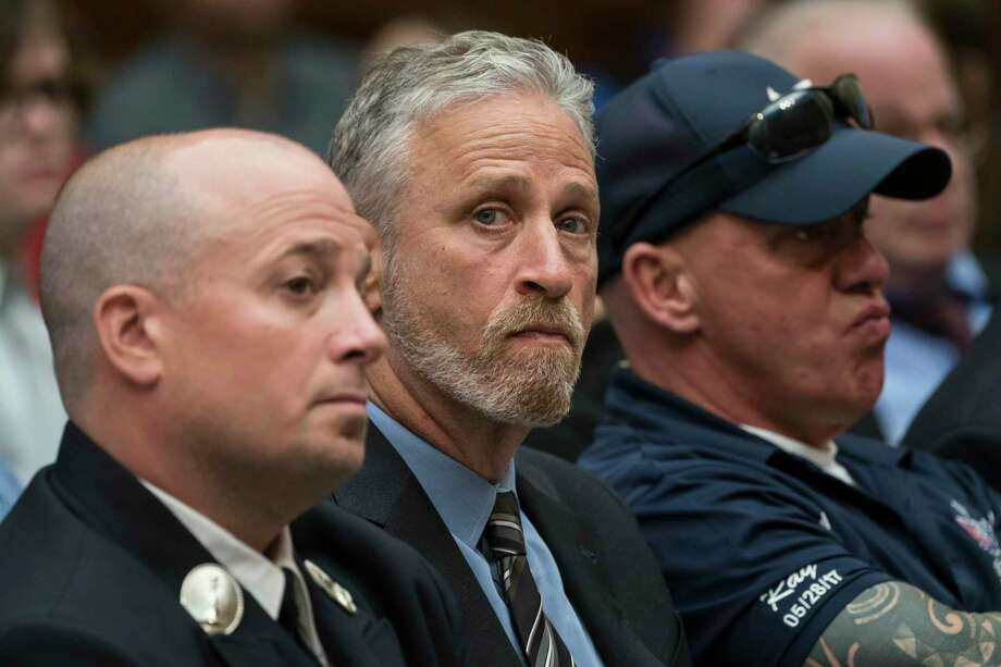 FILE - In a Tuesday, June 11, 2019 file photo, entertainer and activist Jon Stewart, center, lends his support to firefighters, first responders and survivors of the September 11 terror attacks at a hearing by the House Judiciary Committee on Capitol Hill in Washington.Stewart used his buddy Stephen Colbert?s late-night show Monday, June 17, to keep the heat on Senate Majority Leader Mitch McConnell for passage of legislation to replenish a victims' fund for first responders to the 9/11 attacks. (AP Photo/J. Scott Applewhite, File) Photo: J. Scott Applewhite / Copyright 2019 The Associated Press. All rights reserved.