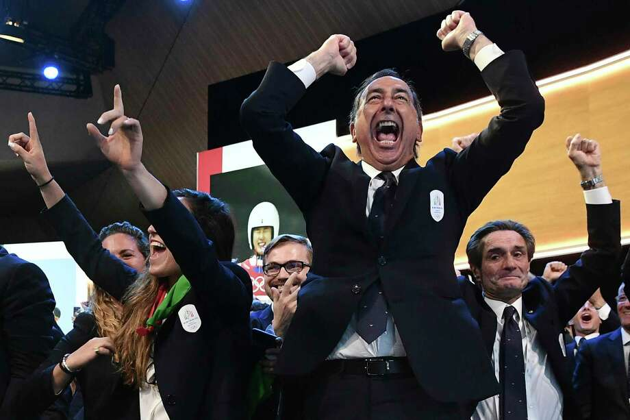 Mayor of Milan Giuseppe Sala and members of Milan-Cortina delegation celebrate after winning the bid to host the 2026 Winter Olympic Games, during the first day of the 134th Session of the International Olympic Committee (IOC), at the SwissTech Convention Centre, in Lausanne, Switzerland, Monday, June 24, 2019. Italy will host the 2026 Olympics in Milan and Cortina d'Ampezzo, taking the Winter Games to the Alpine country for the second time in 20 years. (Philippe Lopez/Pool via AP) Photo: Philippe Lopez / AFP Pool