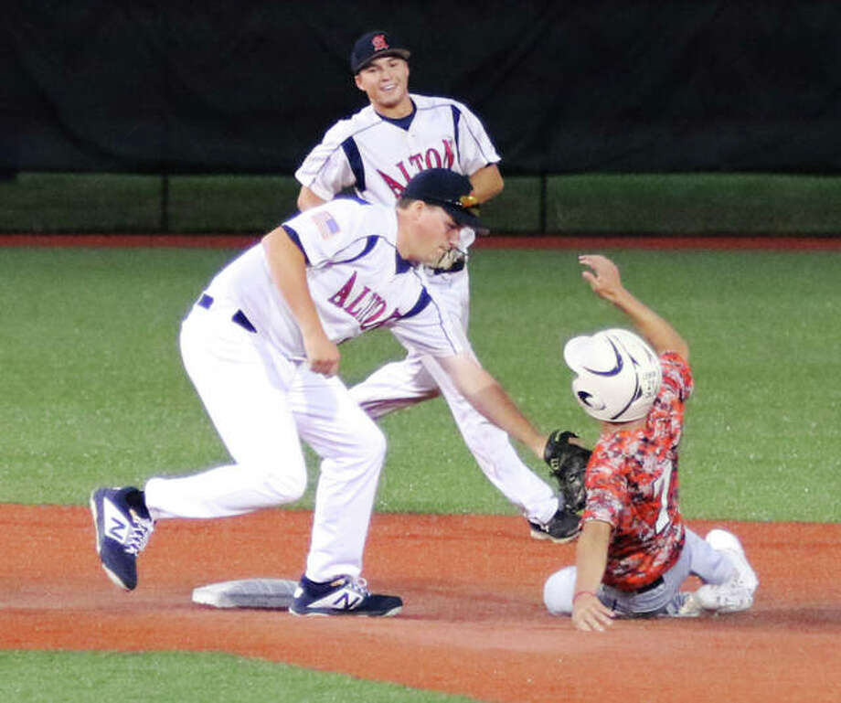 Gillespie's Kaden Lemon (right) is tagged out stealing by Alton second baseman Gage Booten while shortstop Jayce Maag smiles with approval of the out in Alton's 3-0 victory Monday night at SIUE's Roy Lee Field in Edwardsville. Photo: Greg Shashack / The Telegraph