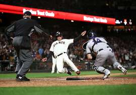 SAN FRANCISCO, CALIFORNIA - JUNE 24:   Joe Panik #12 of the San Francisco Giants is tagged out by Tony Wolters #14 of the Colorado Rockies in the seventh inning at Oracle Park on June 24, 2019 in San Francisco, California. (Photo by Ezra Shaw/Getty Images)