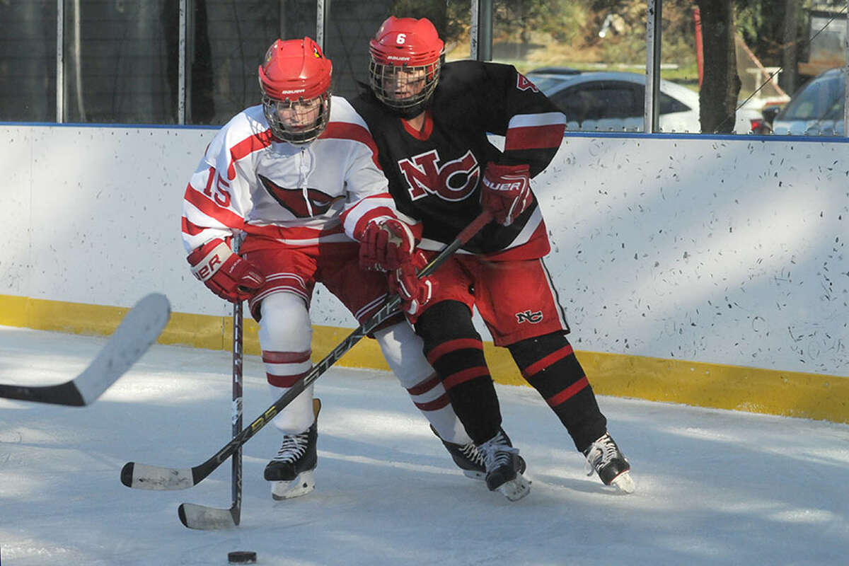 Greenwich's Katie Piotrzkowski (15) and New Canaan's Kaleigh Harden battle along the boards during the Winter Classic at the Greenwich Skating Club on Saturday, Dec. 29, 2018. - Dave Stewart photo