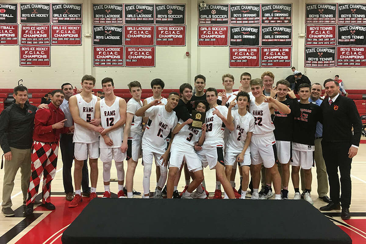 The New Canaan Rams celebrate after defeating Shelton for the championship of the Holiday Classic tournament at NCHS on Saturday. - Terry Dinan photo