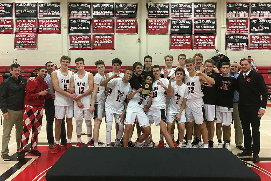 The New Canaan Rams celebrate after defeating Shelton for the championship of the Holiday Classic tournament at NCHS on Saturday. — Terry Dinan photo
