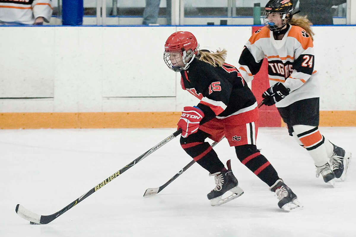 New Canaan freshman Caitlin Tully (15) gets out in front of Ridgefield's Katie Rector (24) during the Rams' 9-0 win at the Winter Garden on Dec. 21. - Scott Mullin photo