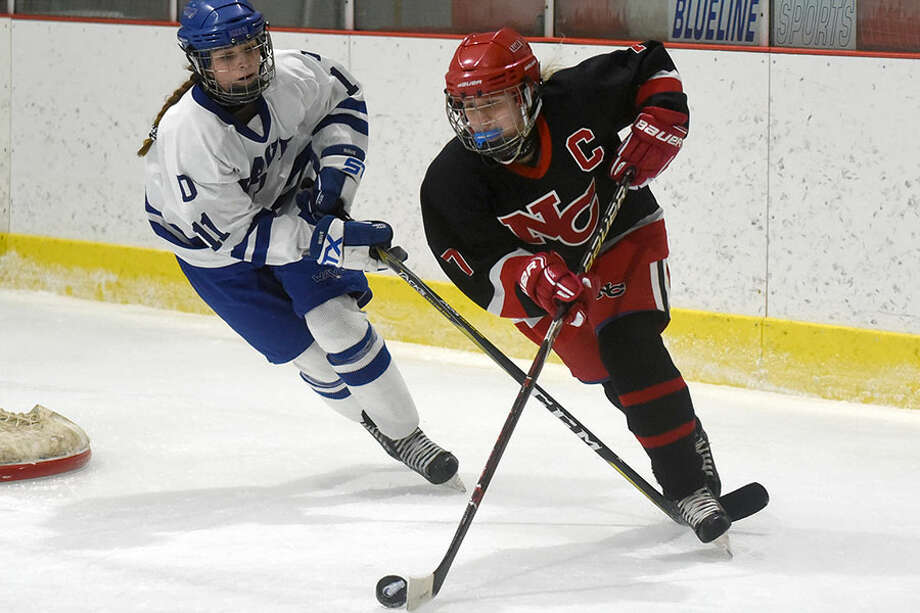 New Canaan's Jess Eccleston gets away from Darien's Kelly Raymond during the Rams' 3-0 win over Darien on Monday, Dec. 17, at the Darien Ice House. — Dave Stewart photo