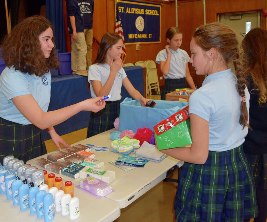 "New Canaan: A Child to child giving ""Operation,"" called Operation Christmas Child recently gathered gifts going global. Students line up to make selections among donated items for gift boxes being sent to children around the world through a project called Operation Christmas Child at St. Aloysius School.— Contributed photo"