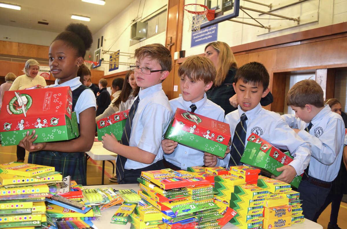 Students make gift selections to send to children around the world as others help with the effort called Operation Christmas Child recently at St. Aloysius School. - Contributed photo