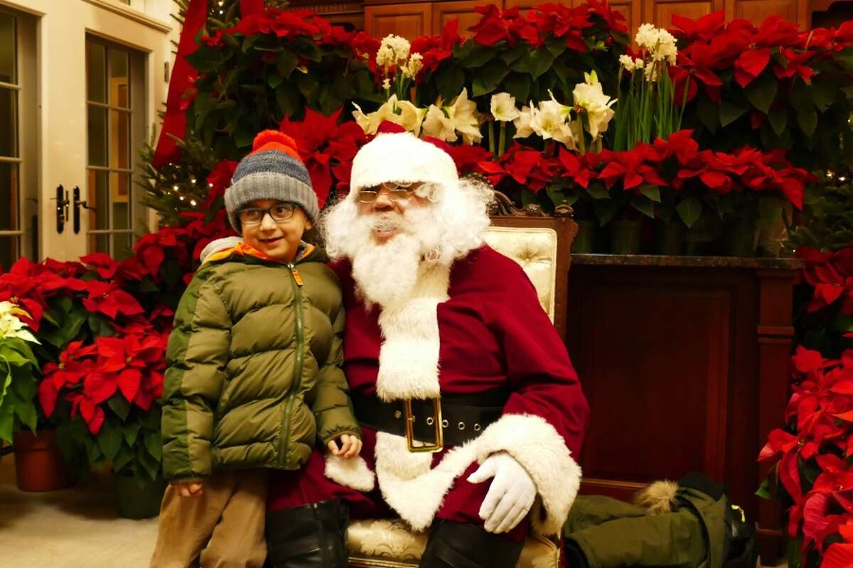Sebastian Reyes smiled at his family while he stood next to Santa in Weed and Duryea hardware store. - Grace Duffield photo