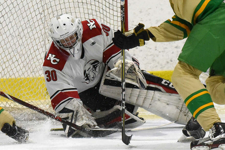 New Canaan goalie Dylan Shane covers the puck for one of his 26 saves in the Rams' 5-2 win over Notre Dame-West Haven Monday at the Darien Ice House. — Dave Stewart photo