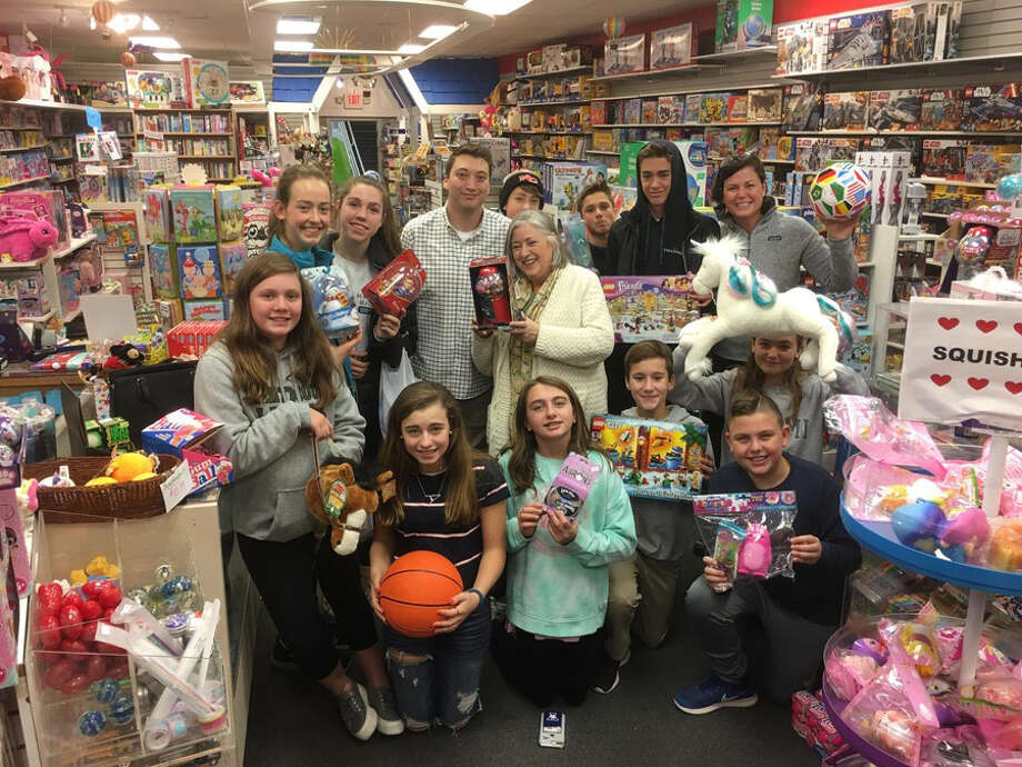 First Presbyterian Church of New Canaan youth shop at New Canaan Toy Store to help Filling in the Blanks fill backpacks for children. — Contributed photo