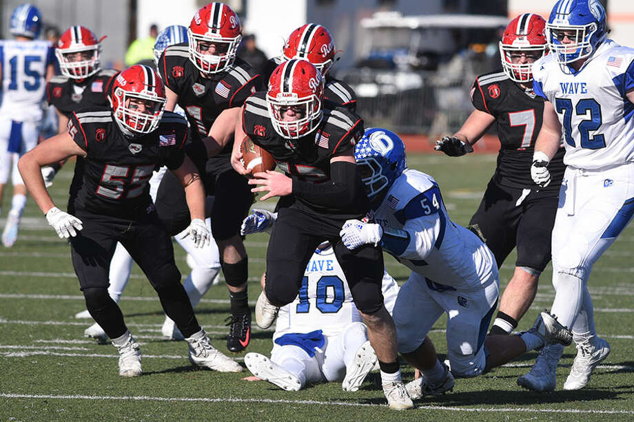 New Canaan's Kieran Buck (12) gets away from a Darien tackler after recovering a fumble in the fourth quarter of the Turkey Bowl in Stamford. Harrison Skyrm (55) knocked the ball loose on the play. — Dave Stewart photo