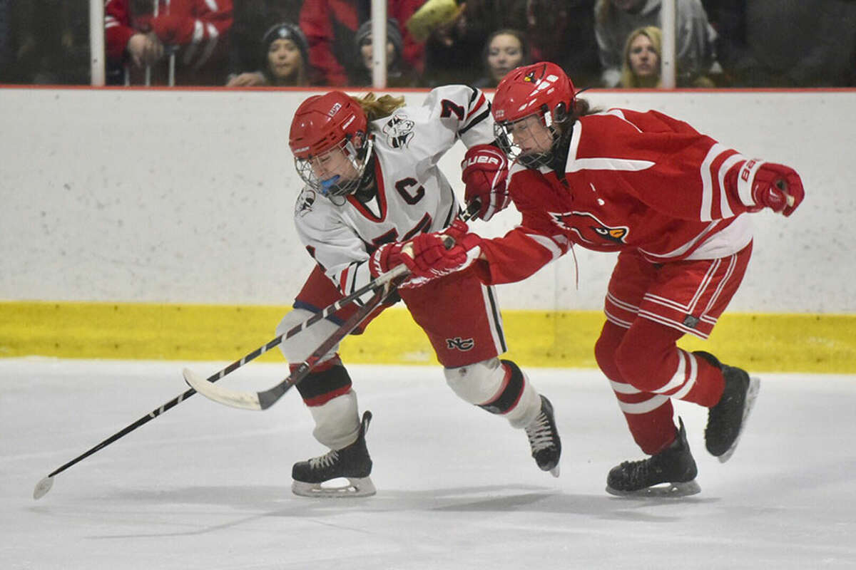 New Canaan's Jess Eccleston and Greenwich's Katie Piotrzkowski battle for the puck during the FCIAC girls hockey final at the Darien Ice House on Saturday, Feb. 23. - Dave Stewart/Hearst Connecticut Media