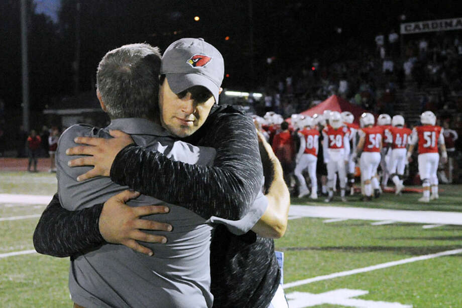 Greenwich High School head football coach John Marinelli, right, hugs his father, Lou Marinelli, the head coach of the New Canaan High School football team at the end of a game in Greenwich on Oct. 14, 2017. — Bob Luckey Jr. Photo