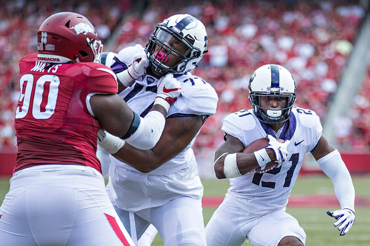 Lucas Niang (77) blocks for running back Kyle Hicks during the TCU Horned Frogs' game against the Arkansas Razorbacks at Donald W. Reynolds Razorback Stadium on Sept. 9, 2017 in Fayetteville, Arkansas. The Horn Frogs defeated the Razorbacks 28-7 - Photo by Wesley Hitt/Getty Images