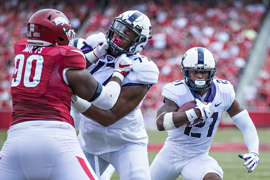 Lucas Niang (77) blocks for running back Kyle Hicks during the TCU Horned Frogs' game against the Arkansas Razorbacks at Donald W. Reynolds Razorback Stadium on Sept. 9, 2017 in Fayetteville, Arkansas. The Horn Frogs defeated the Razorbacks 28-7 — Photo by Wesley Hitt/Getty Images / 2017 Getty Images