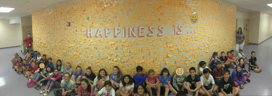"New Canaan Public Schools recently presented their health curriculum update to the Board of Education. This ""Happiness Is"" wall outside a classroom at Saxe Middle School is where students place affirmations on sticky notes to promote a constructive mindset. — Contributed photo"
